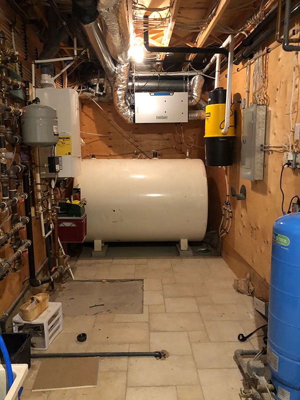 Photo of a furnace oil tank in basement of house in Harrowsmith, Ontario